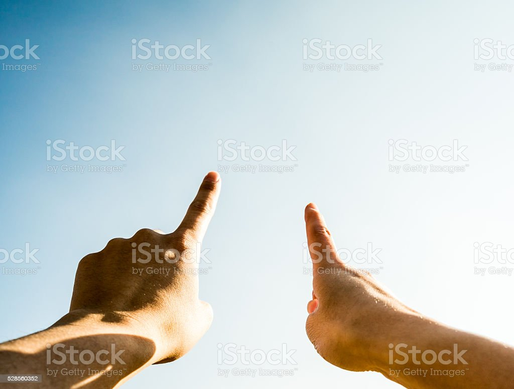 People pointing at blue sky stock photo