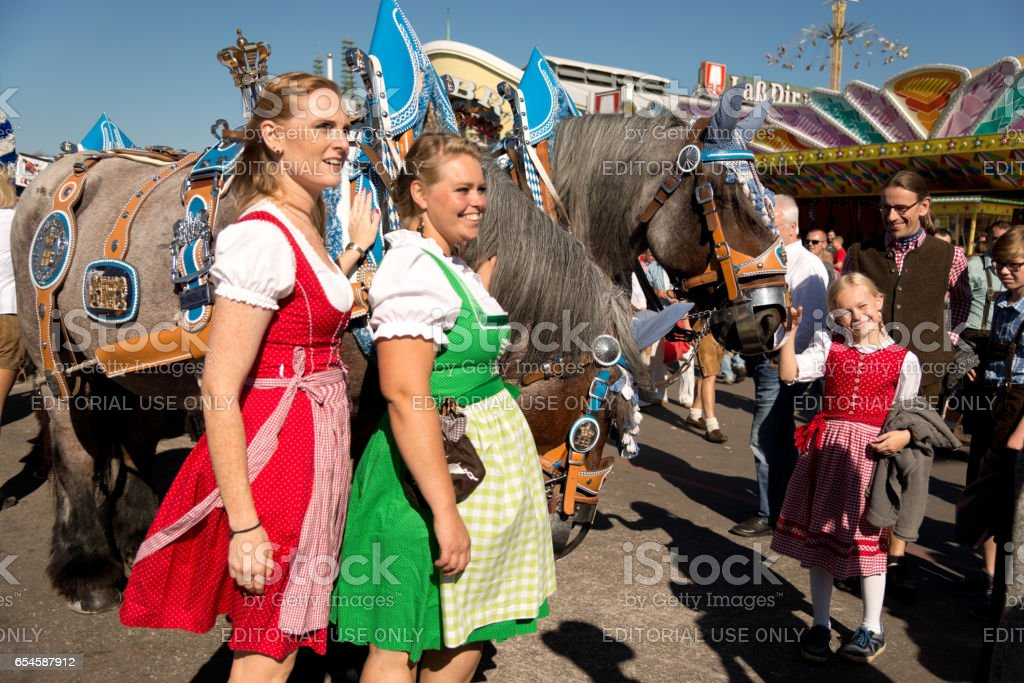 People posing in front of horses at the Oktoberfest stock photo