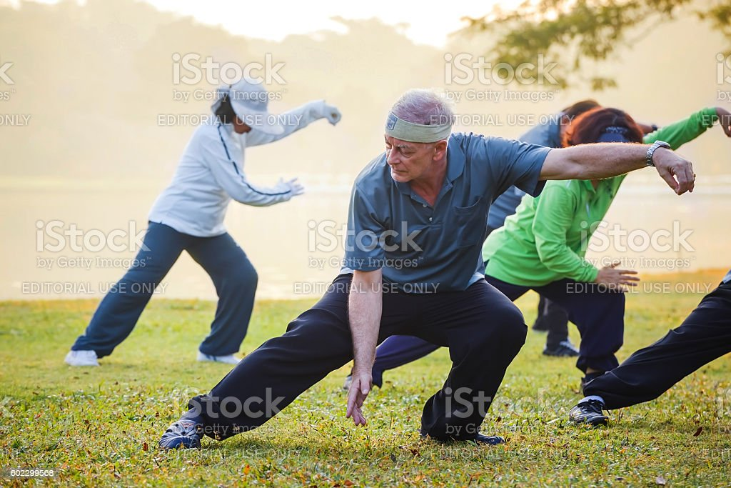 people practice Tai Chi Chuan in a park stock photo