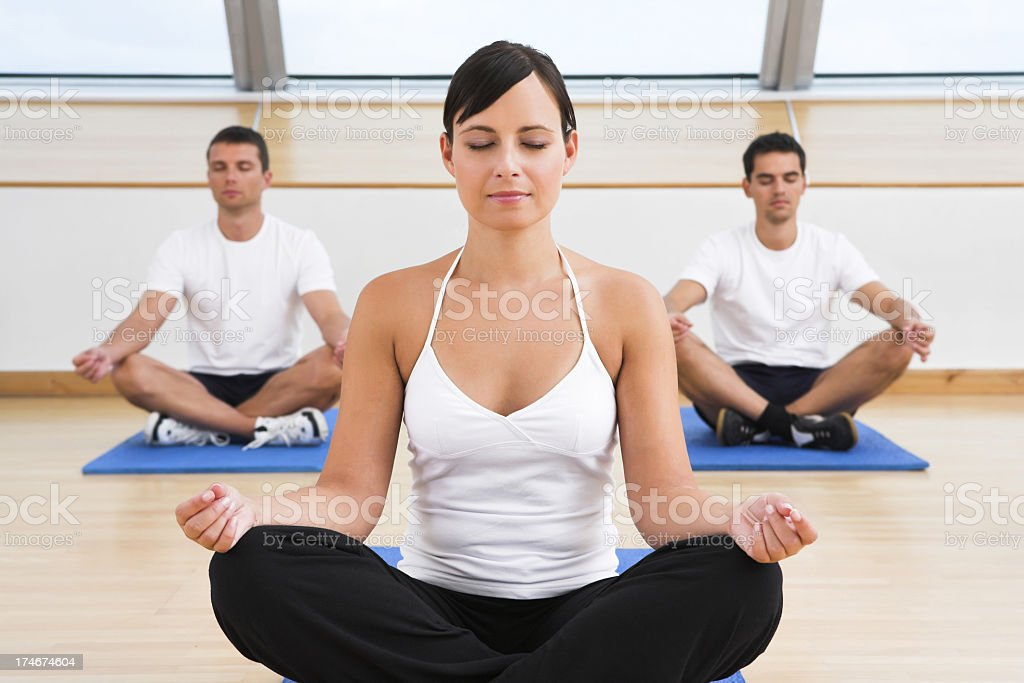 People practicing yoga at fitness club stock photo