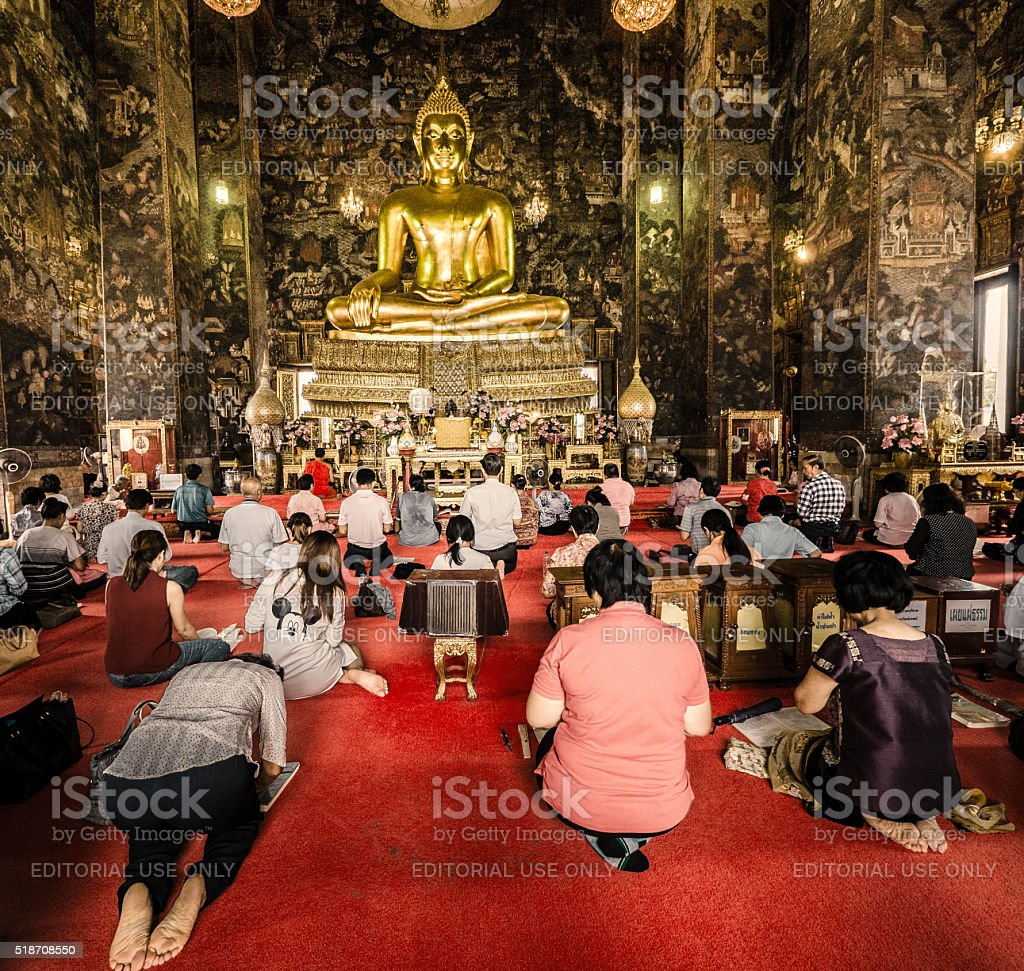 People praying at buddhist temple Wat Suthat stock photo
