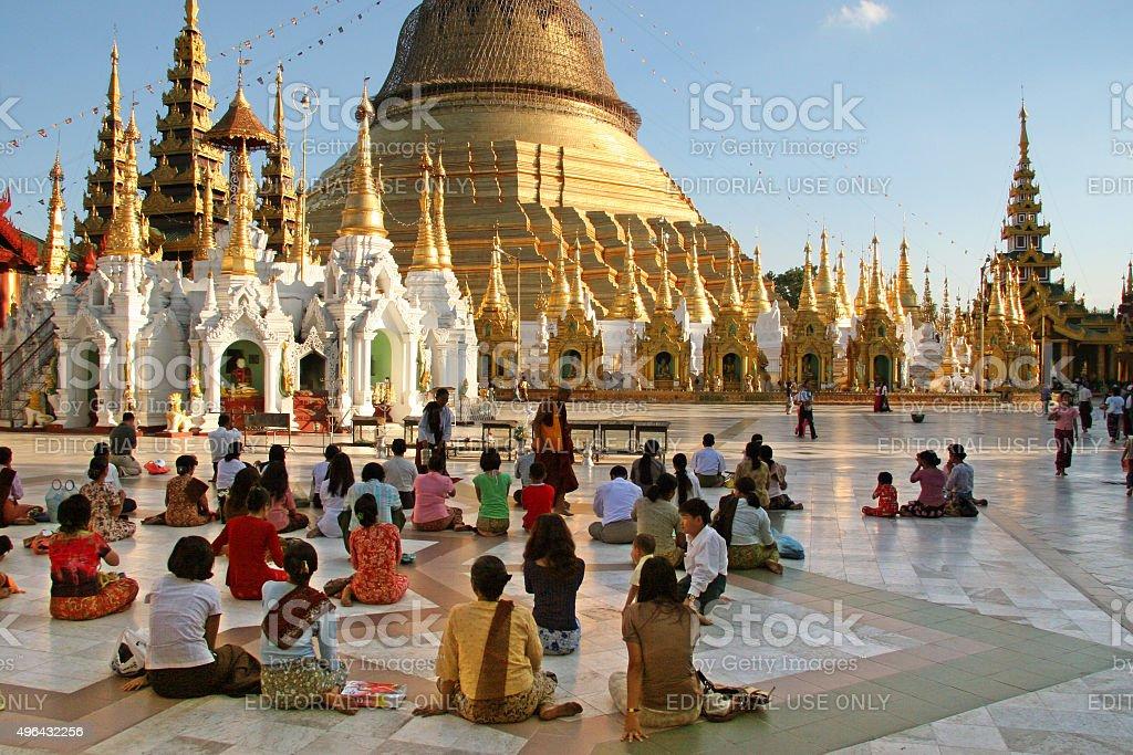 People praying in front of Shwedagon Pagoda in Yangon, Myanmar stock photo