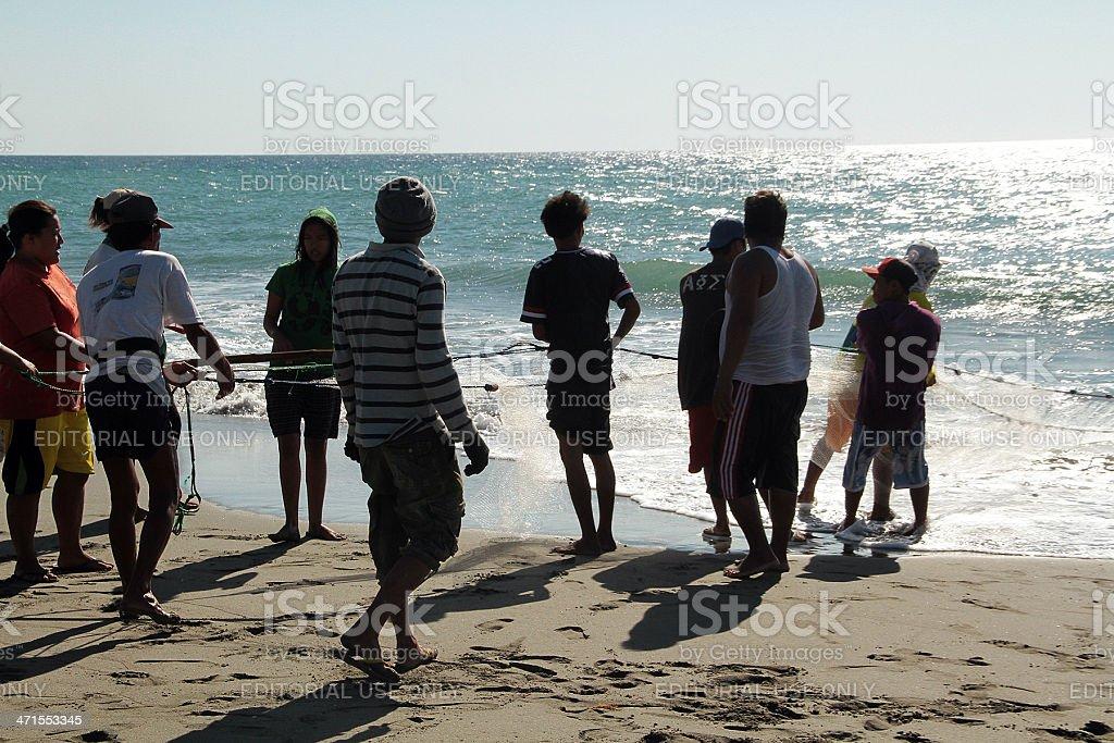 Persone Tirare una rete di pesca alla costa, spiaggia di Mindoro foto stock royalty-free