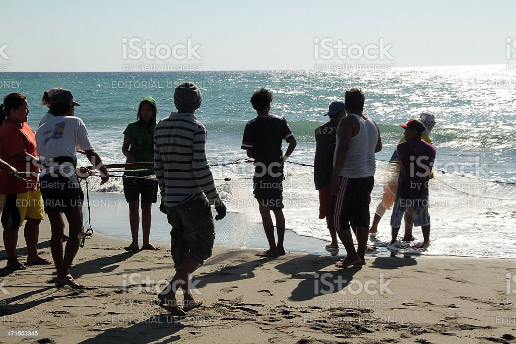 People Pulling a Fishing Net to Shore, Mindoro Beach stock photo