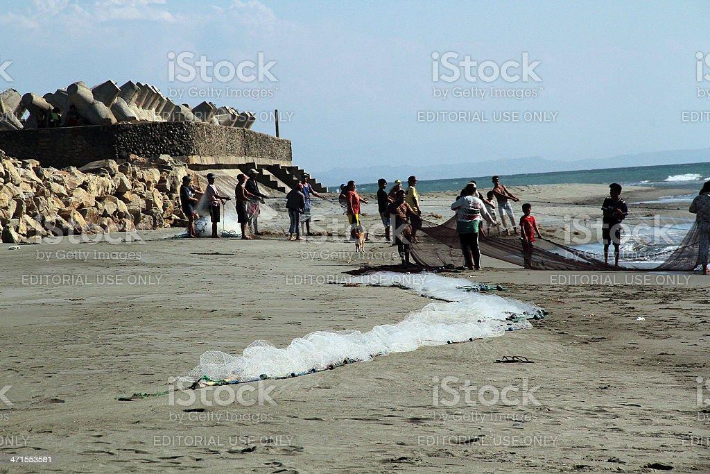 Persone Tirare una rete di pesca alla spiaggia, Vigan foto stock royalty-free