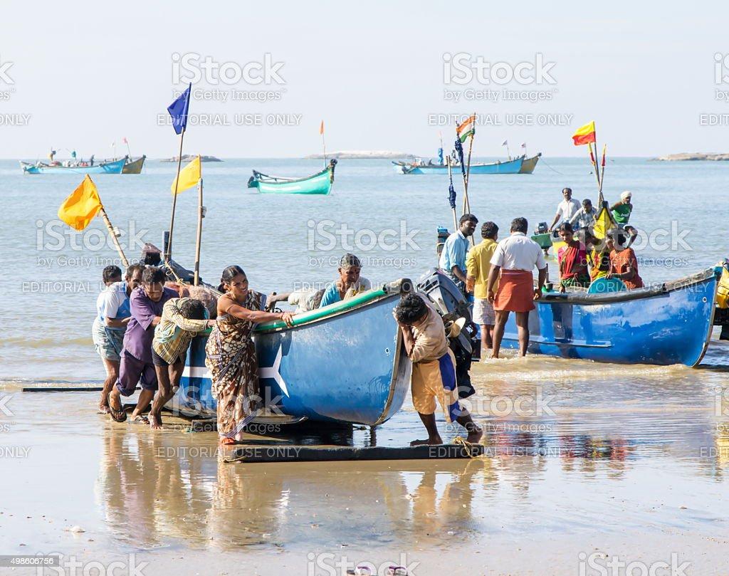 People pushing fishing boat, Murudeshwar, Karnataka, India stock photo
