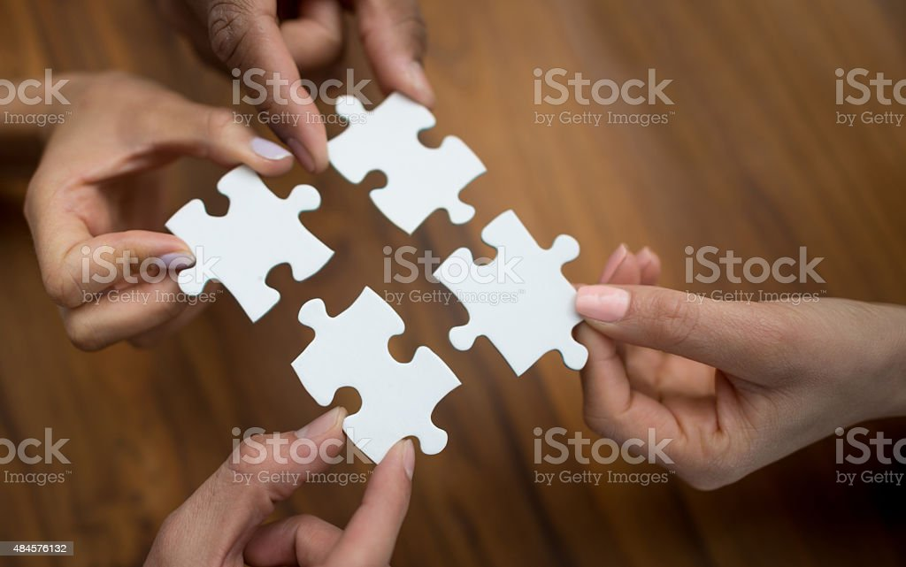 People putting pieces of a puzzle together stock photo
