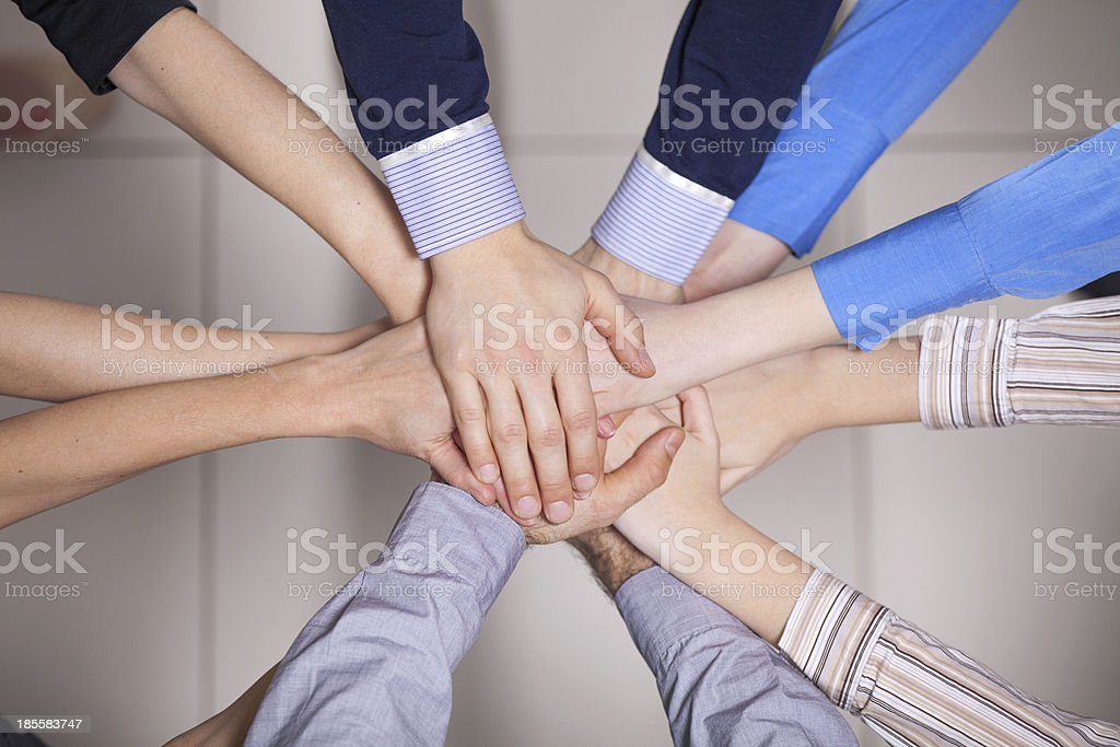 People putting their hands together in a circle stock photo