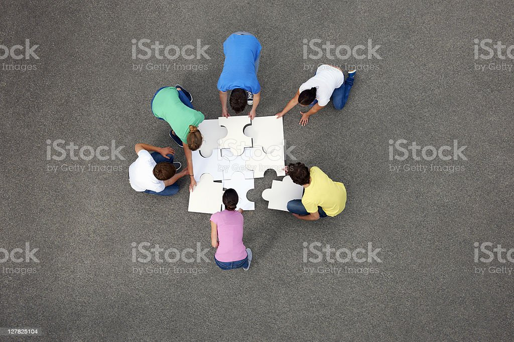 People putting together jigsaw puzzle royalty-free stock photo