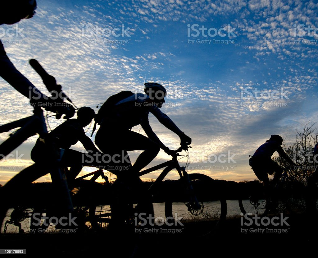 People racing in a bike ride at sunset silhouettes royalty-free stock photo