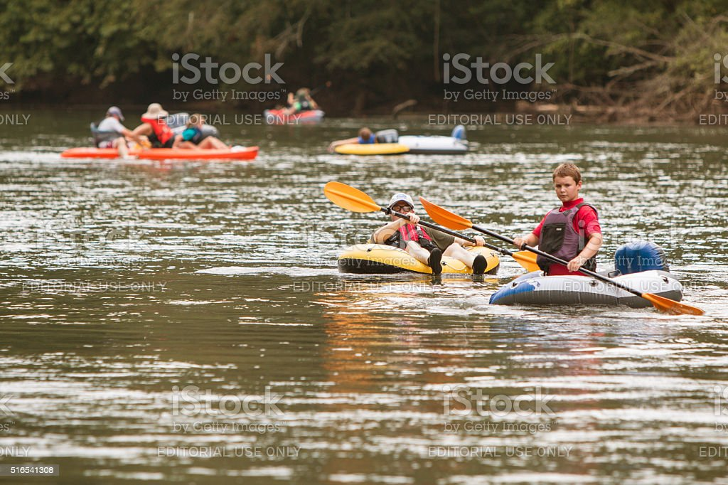 People Raft And Kayak Along River On Hot Summer Day stock photo