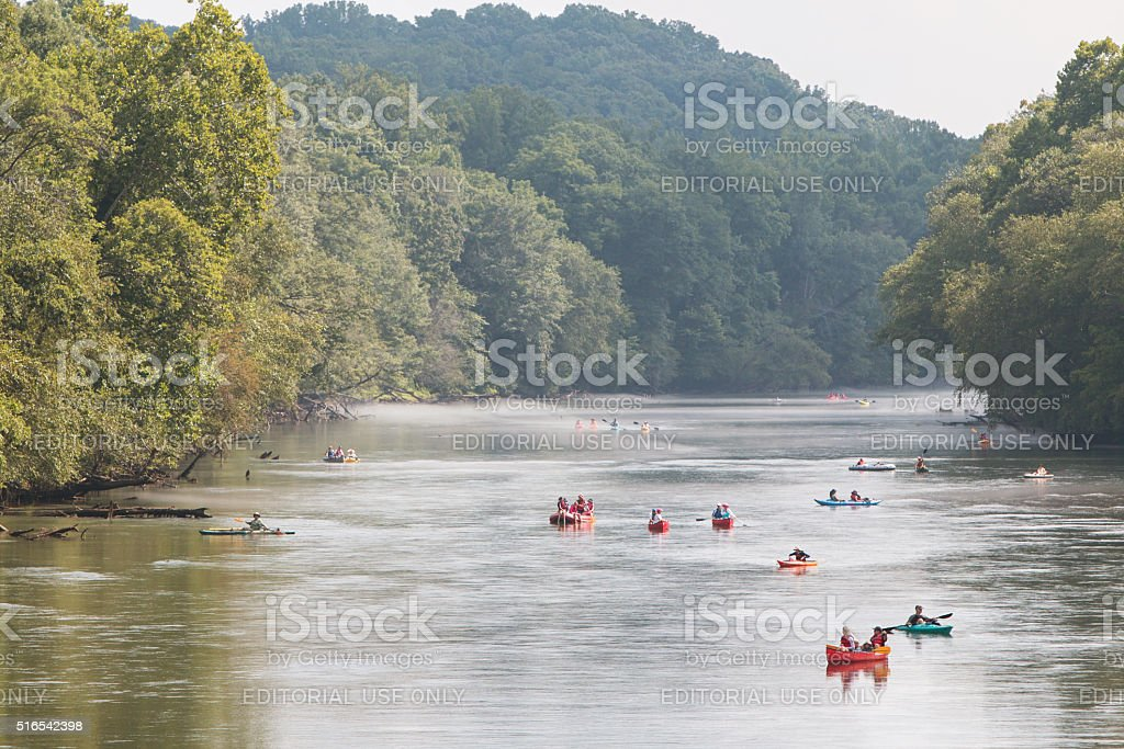 People Raft And Kayak Down River On Hot Summer Day stock photo