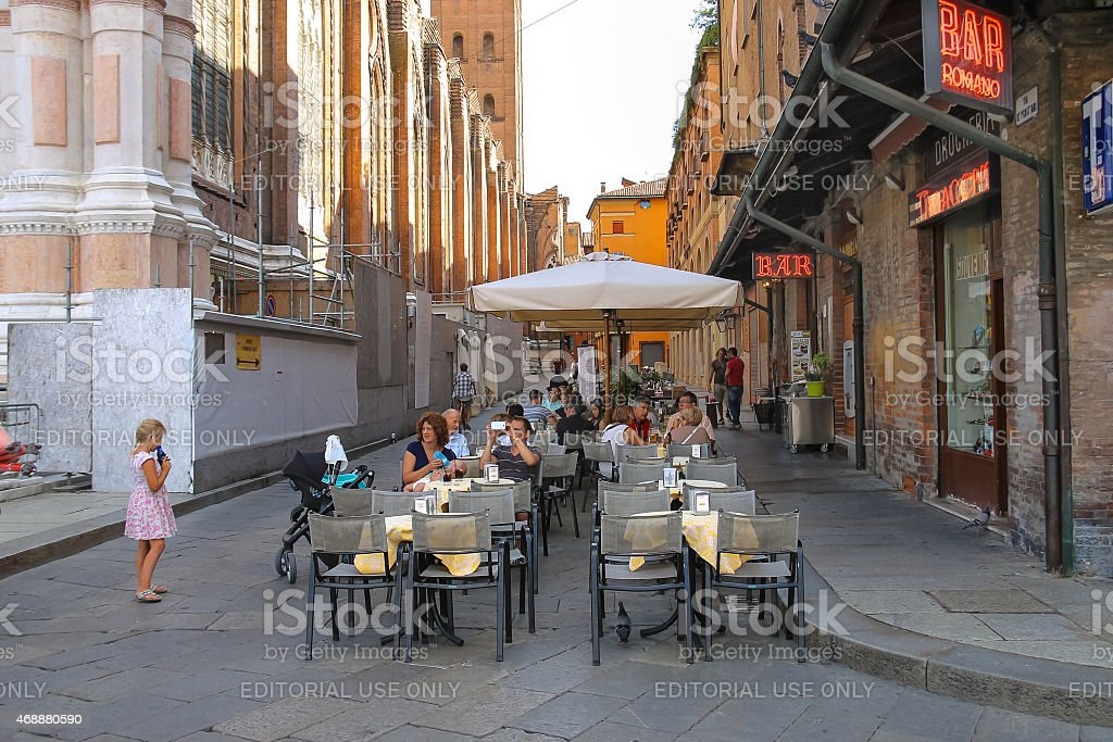 People relax behind little tables of the restaurant stock photo
