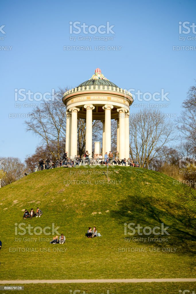 People relax while sunbathing at the Monopteros in the Englischer Garten stock photo