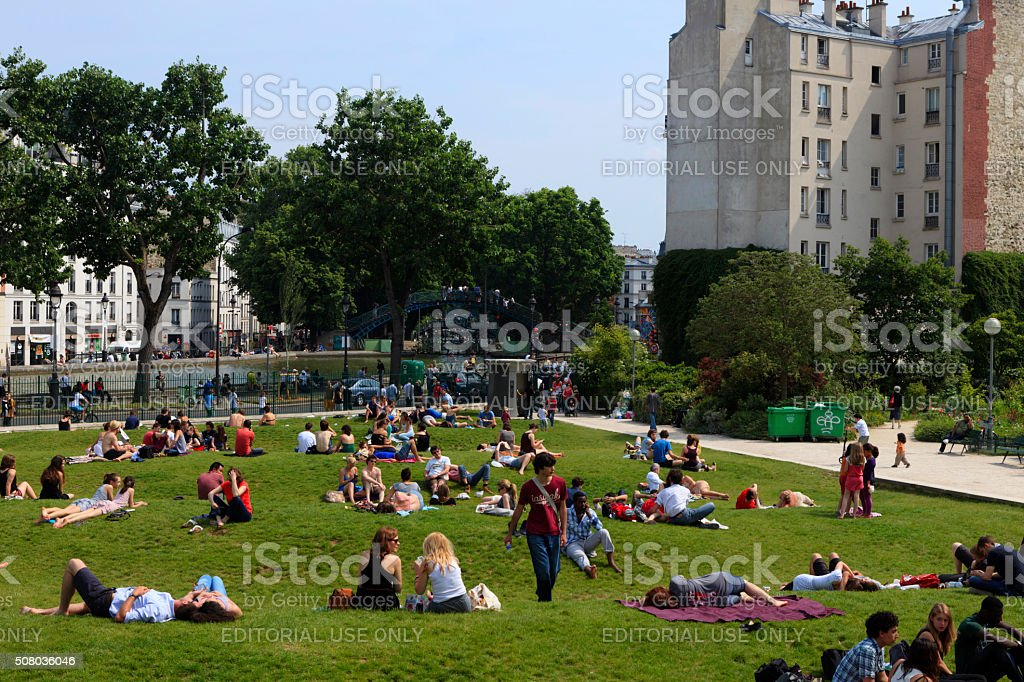 people relaxing at Jardin Villemin in Paris stock photo