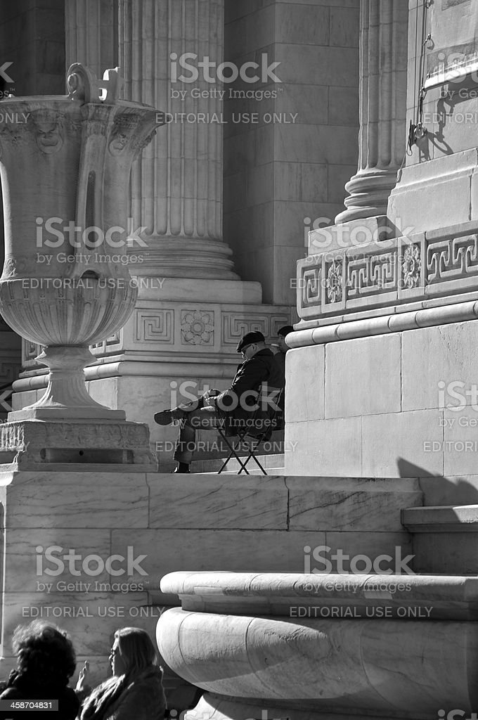 People relaxing at New York City Public Library building entrance stock photo