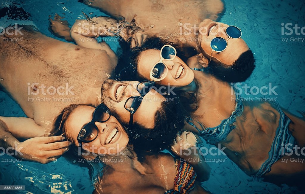 People relaxing in a swimming pool. stock photo