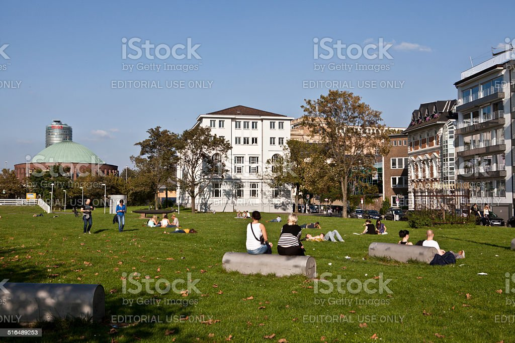 people relaxing in city park stock photo