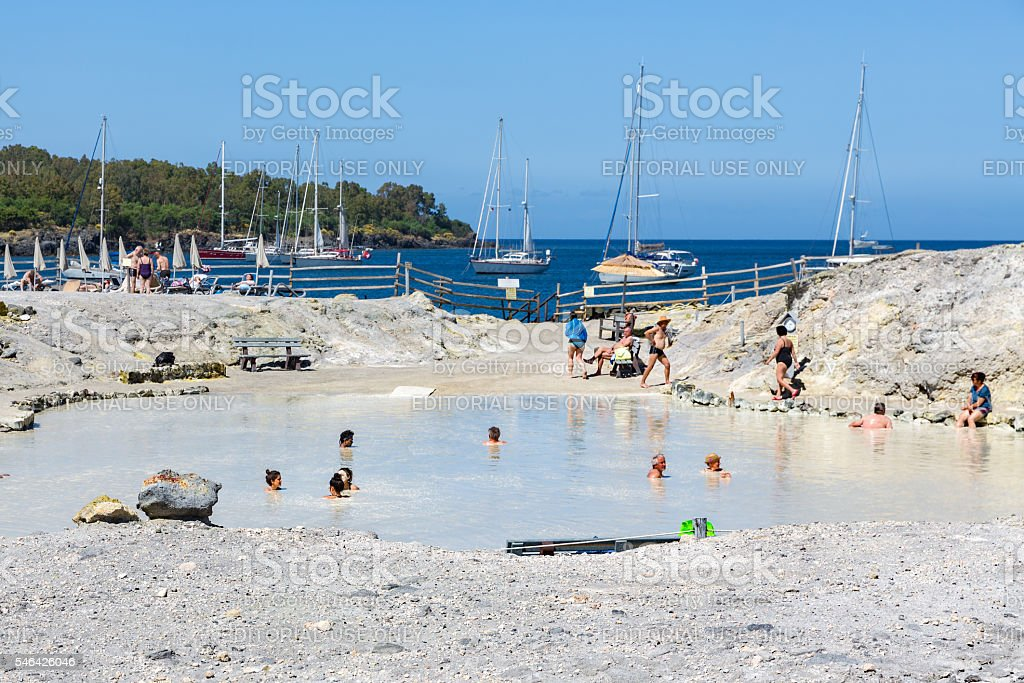 People relaxing in healthy mud pool at Aeolian Islands, Italy stock photo