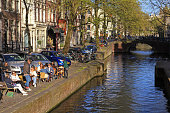 People relaxing in sidewalk cafe by river canal in Amsterdam