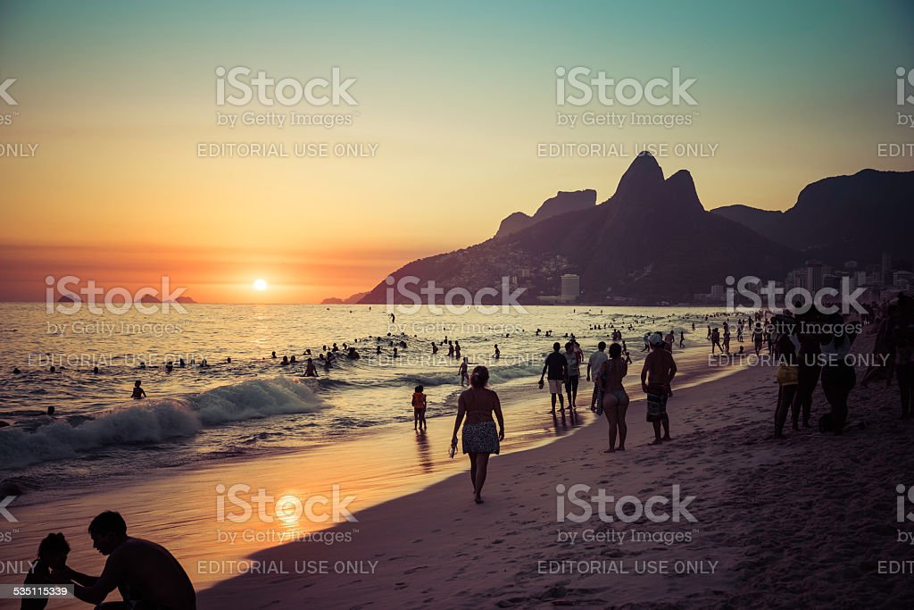 People relaxing on Ipanema Beach during beautiful hot summer sunset. stock photo