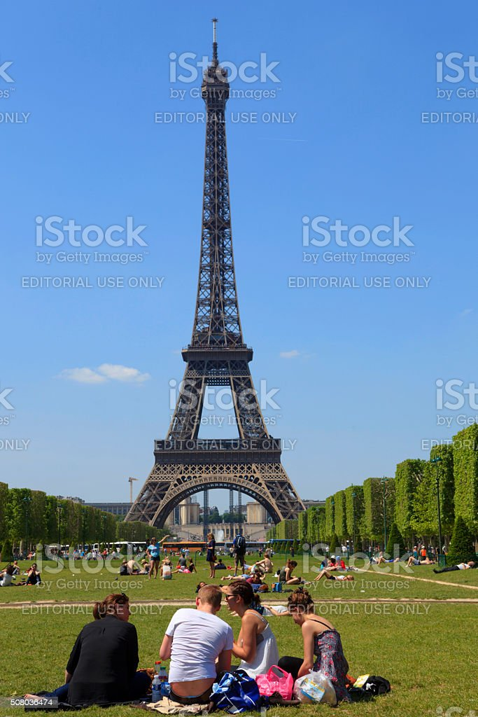 people relaxing under the Eiffel Tower stock photo