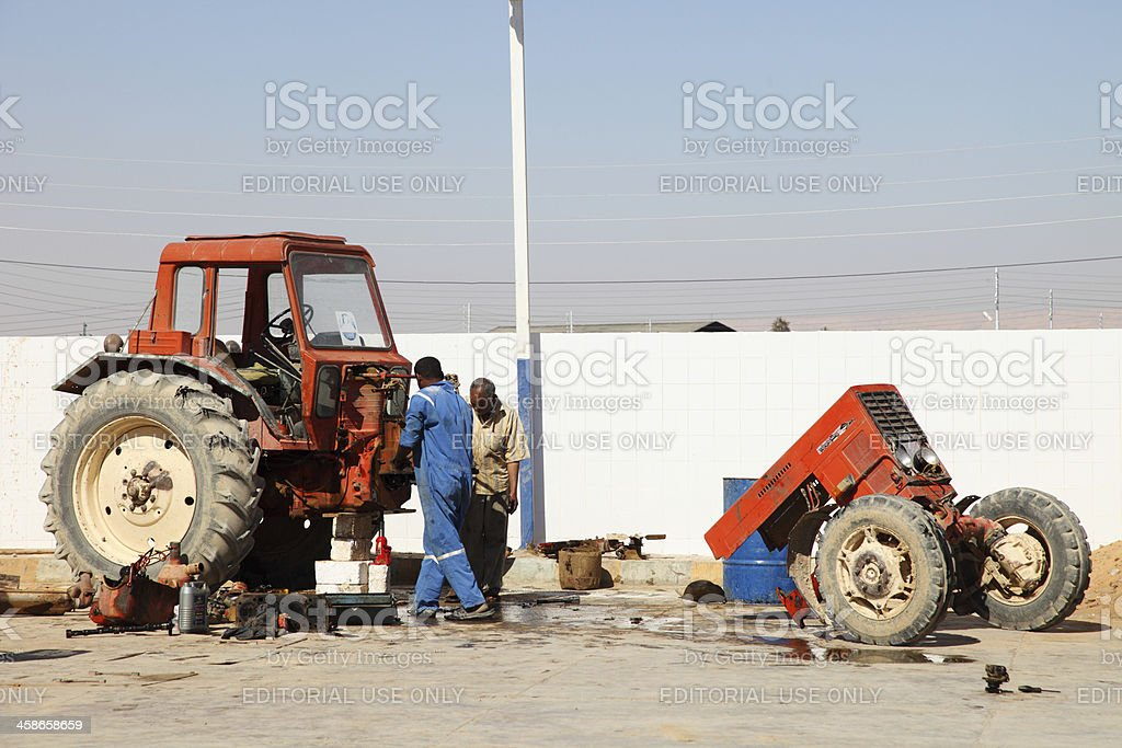 People repairing a tractor stock photo