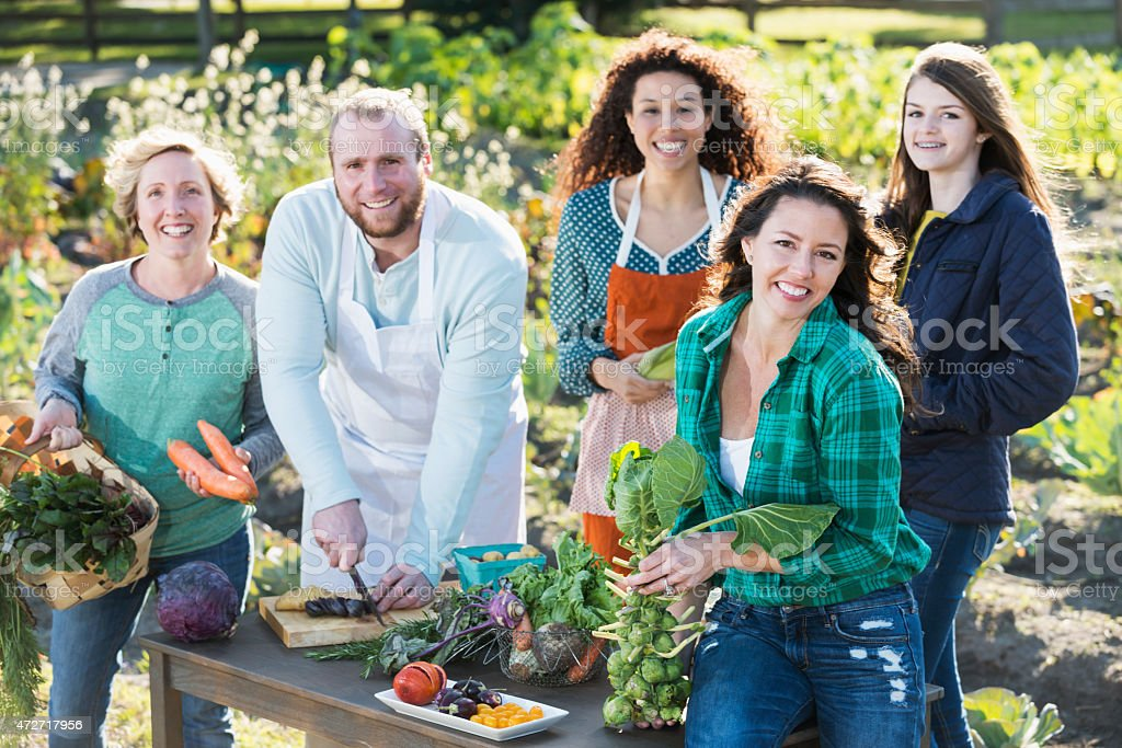 A group of five people preparing fresh, organic vegetables on a table...