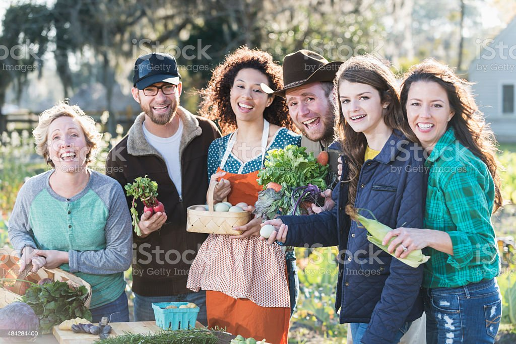 A group of six people with fresh, organic vegetables and eggs beside...
