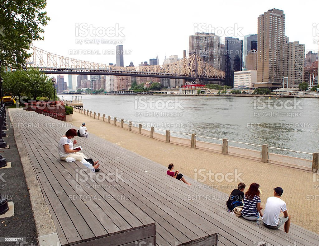 People resting in Roosevelt Island with Queensborough bridge stock photo