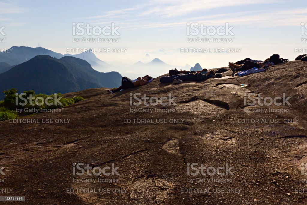 People resting on top of Pedra da Gavea stock photo
