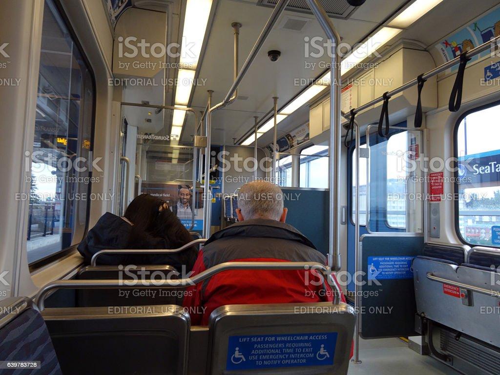 People ride Sound Transit light rail train stock photo