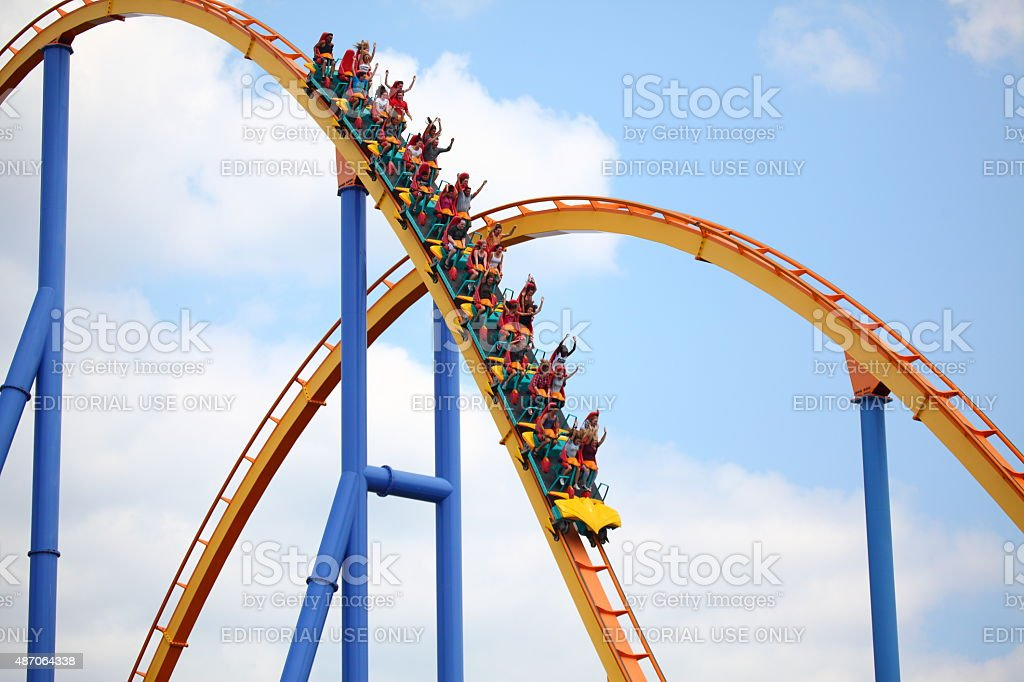 People riding a rollercoaster in an amusement park stock photo
