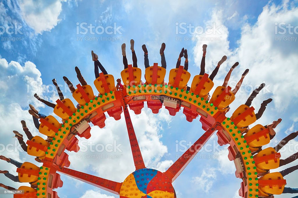 People riding with fun on extreme attraction in amusement park stock photo