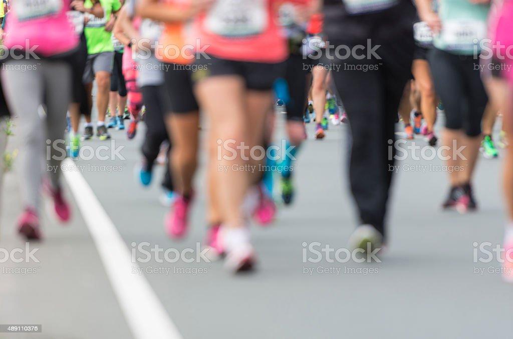 People running a city marathon stock photo