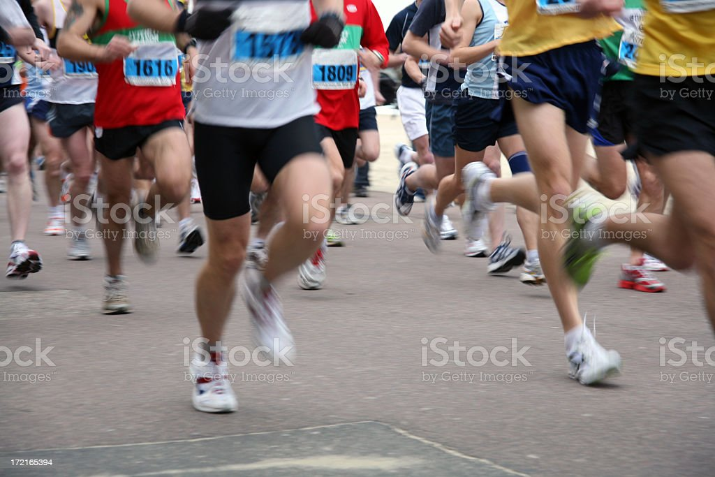 People running a marathon with a blur of their feet stock photo