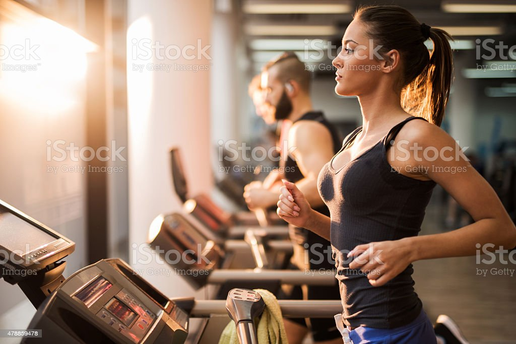 People running on a treadmill in health club. stock photo