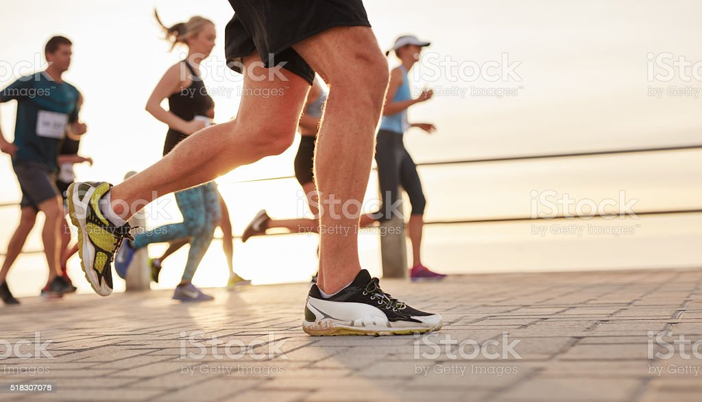 People running on road by the sea stock photo
