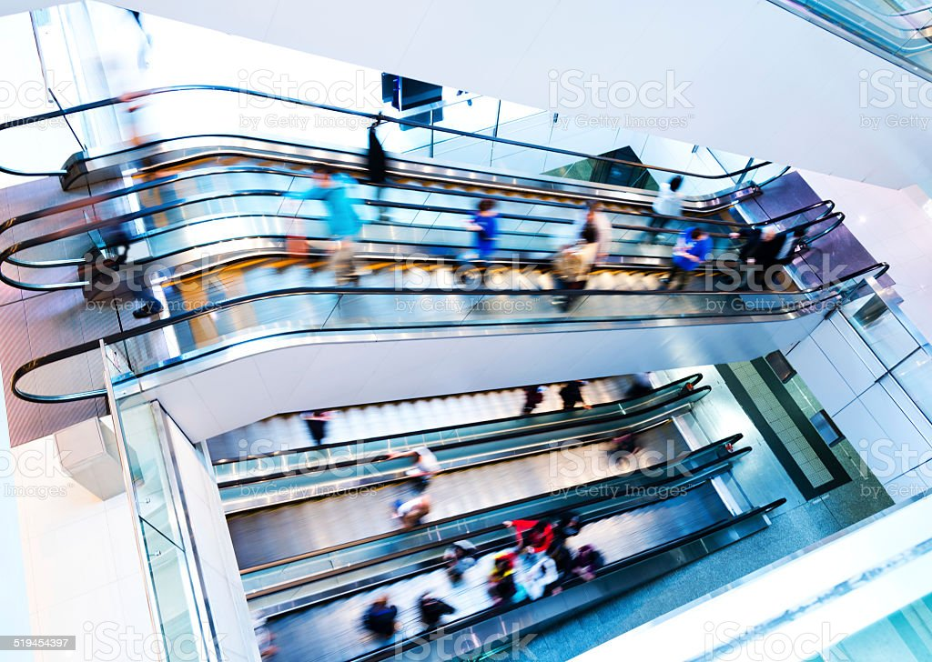 people rushing in escalators stock photo