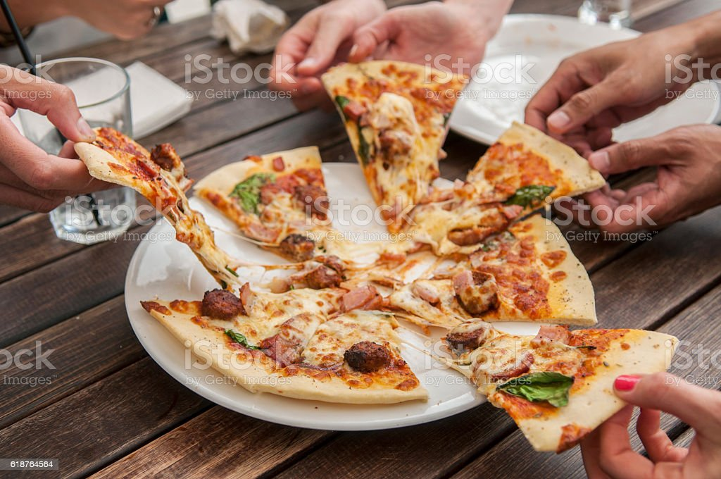 People sharing a pizza stock photo