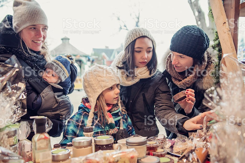 People shopping at an outdoors public market in winter. stock photo