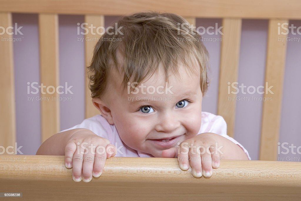 People - Shy 10 Month Old Baby Girl in Crib stock photo