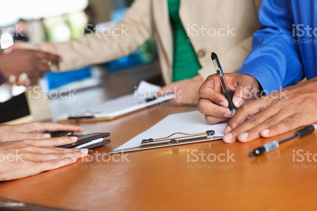 People signing in or registering at registration desk, close up stock photo