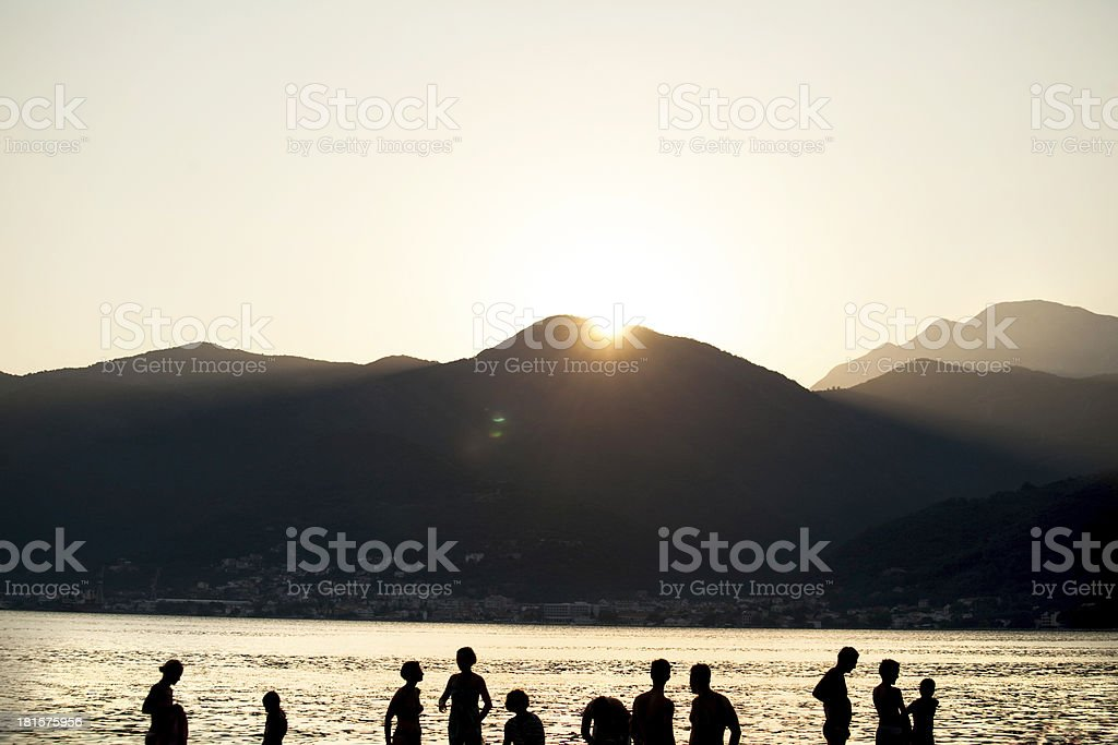 people silhouetes on the beach royalty-free stock photo