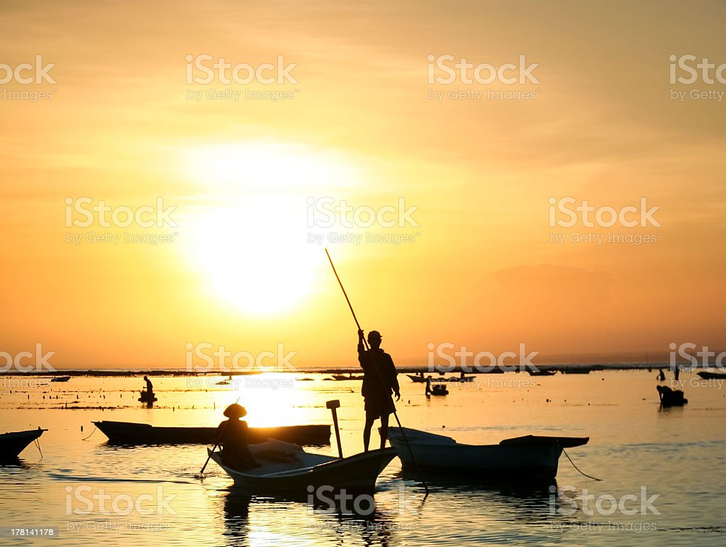 people silhouetted by sunset bali indonesia stock photo