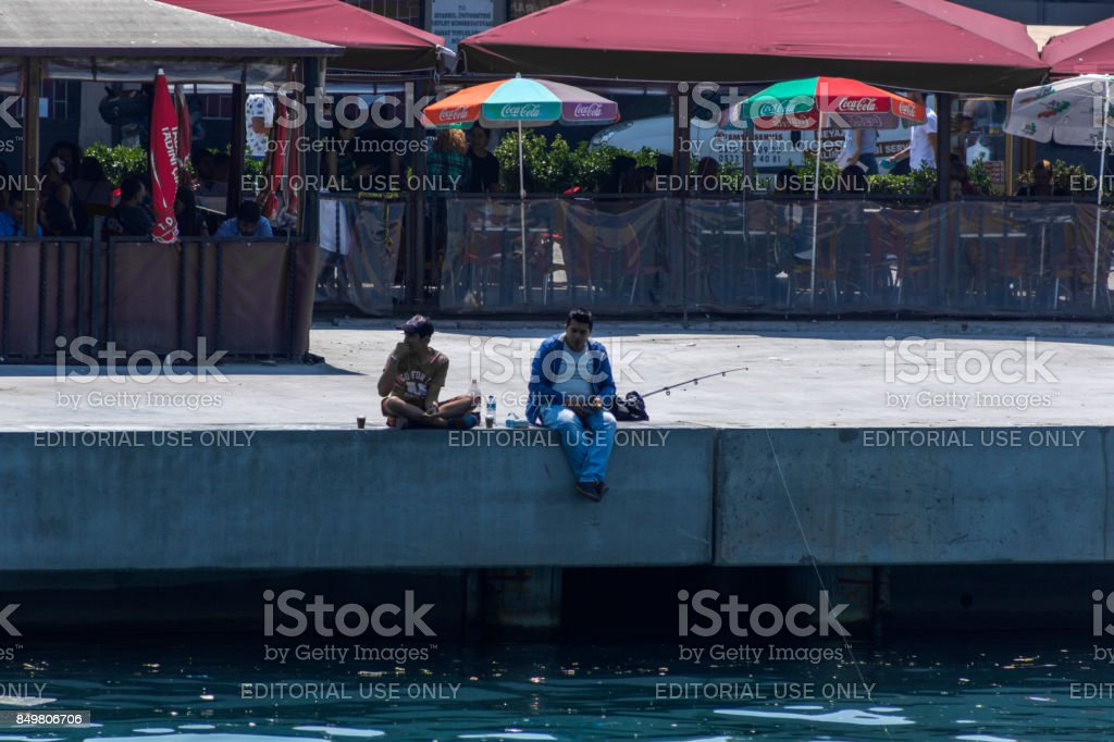 people sitting and catching fish by bosphorus at coast of karakoy istanbul turkey stock photo