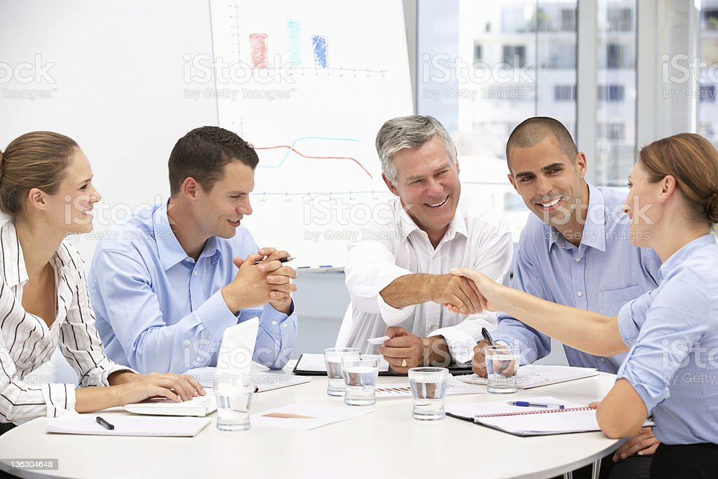 People sitting around a table with papers stock photo