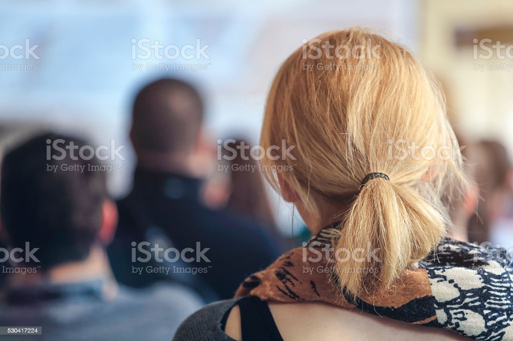 People sitting at a big conference hall during video-presentation stock photo