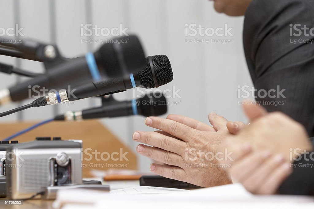 People sitting at microphones in a business conference stock photo