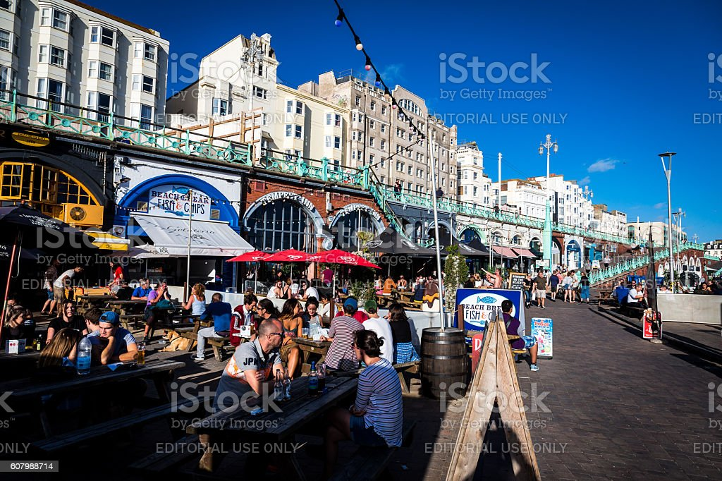 People sitting at picnic tables on seafront, Brighton, UK stock photo